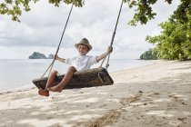 Thailand, Ko Yao Noi, happy boy on a swing on the beach — Stock Photo