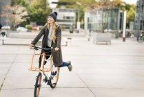 Mulher feliz andar de bicicleta na cidade — Fotografia de Stock