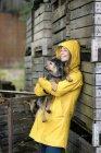 Улыбающаяся женщина на ферме стоит у деревянных коробок и держит собаку — стоковое фото
