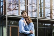 Affectionate couple embracing in front of their home — Stock Photo