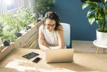 Улыбающийся фрилансер сидит за столом в лофте и смотрит на ноутбук — стоковое фото