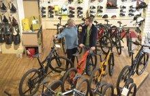 Vendedor ajudando cliente na loja de bicicletas — Fotografia de Stock