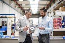 Hommes d'affaires lors d'une réunion avec un produit dans le hall de production — Photo de stock