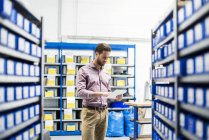 Businessman using tablet in storage — Stock Photo