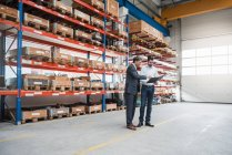 Two men walking and talking in factory shop floor — Stock Photo