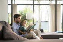 Отец и сын читают книгу на диване дома — стоковое фото