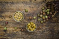 Two jars of preserved gooseberries and gooseberries on wooden background — стоковое фото