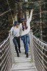 Deux jeunes femmes heureuses marchant ensemble sur une suspension — Photo de stock