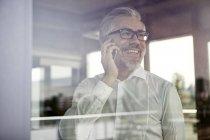 Homme d'affaires riant à la fenêtre parlant sur le téléphone portable — Photo de stock