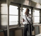 Businessman on a ferry looking out of window — Stock Photo