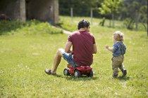 Отец со своим маленьким сыном на улице играют вместе — стоковое фото