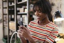 Портрет улыбающейся девушки на чердаке с помощью мобильного телефона — стоковое фото