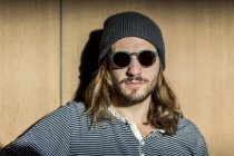 Portrait of bearded man with long hair wearing sunglasses and wooly hat — Stock Photo