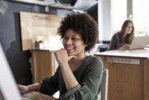 Щаслива молода жінка, використовуючи комп'ютер в сучасному офісі — стокове фото