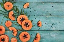 Papaya en rodajas sobre madera azul - foto de stock