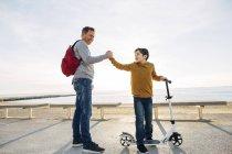 Padre e figlio con scooter che si stringono la mano sul lungomare al tramonto — Foto stock