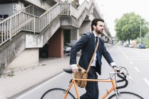 Businessman with bicycle walking on the street — Stock Photo
