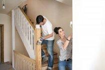 Jeune couple rénovant une nouvelle maison, escalier de peinture — Photo de stock