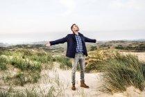 Мужчина, стоящий в дюнах с распростертыми руками — стоковое фото