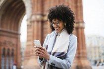 Espanha, Barcelona, mulher feliz usando telefone celular com fones de ouvido na rua — Fotografia de Stock