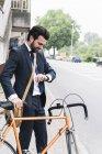 Усміхнений бізнесмен з велосипедом на вулиці перевірка часу — стокове фото