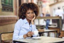Portrait de femme souriante avec coiffure afro assis dans un café extérieur — Photo de stock