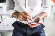 Hands of businessman using cell phone in office — Stock Photo