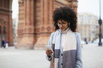 Espagne, Barcelone, femme positive utilisant le téléphone portable avec des écouteurs sur la rue — Photo de stock