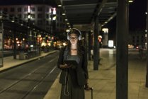 Portrait of young woman with headphones and tablet waiting at station by night — Stock Photo