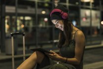 Smiling young woman with headphones and tablet waiting at station by night — Stock Photo