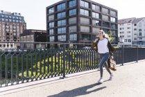 Young woman running on bridge, listening music with headphones — Stock Photo