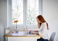 Femme rousse assise à table devant la fenêtre à l'aide d'un ordinateur portable — Photo de stock