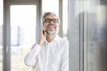 Laughing businessman at the window talking on cell phone — Stock Photo