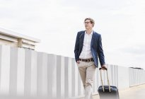 Confident businessman with rolling suitcase walking at parking garage — Stock Photo