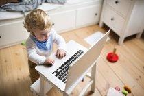 Niño en casa jugando con el ordenador portátil - foto de stock