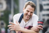 Portrait of happy man with takeaway coffee in the city — Stock Photo