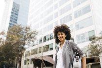 Retrato de mulher sorridente com saco ao ar livre — Fotografia de Stock