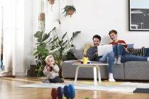 Родители сидят на диване, пользуются ноутбуком, пока дочь играет на полу — стоковое фото