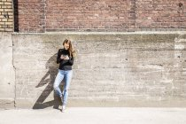 Mujer con apoyado contra la pared usando el teléfono celular - foto de stock