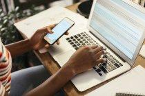 Femme assise au bureau avec smartphone et ordinateur portable, vue partielle — Photo de stock