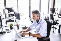 Homme d'affaires mature assis au bureau et utilisant un ordinateur portable — Photo de stock