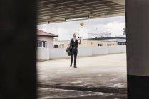 Empresário vomitando basquete na garagem — Fotografia de Stock