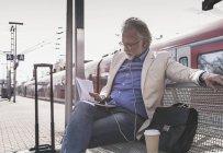 Зрелый бизнесмен, сидящий на вокзале с мобильным телефоном, наушниками и ноутбуком — стоковое фото