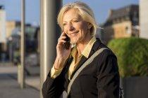 Sonriente mujer de negocios senior en el teléfono celular al aire libre - foto de stock