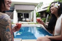 Dos mujeres felices tomando cócteles en la piscina - foto de stock
