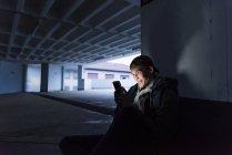 Sorrindo homem olhando para brilhante smartphone na garagem de estacionamento — Fotografia de Stock