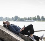 Mature man with headphones and smartphone at Rhine riverbank — Foto stock