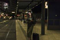 Mulher nova com os auscultadores e a tabuleta que esperam na estação em a noite — Fotografia de Stock