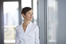 Smiling businesswoman in office looking sideways — Stock Photo