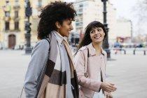 Spain, Barcelona, two happy women walking in city — Stock Photo